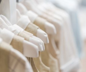 a close up of identical baby outfits all hung in a row on satin hangers