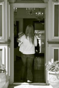 a black and white photo of a woman and her baby walking in the door of a boutique and you can see crystal chandeliers hanging above her from the ceiling