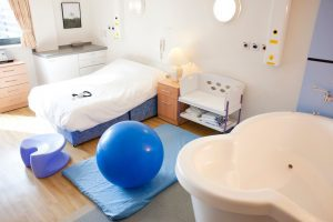 an empty birthing room with a tub and a yoga ball next to an empty bed