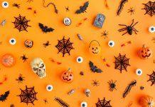 Halloween skulls, spider webs, and jack-lanterns scattered on an orange background