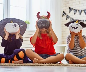 children in costumes sitting criss cross on the floor, holding halloween painted pumpkins in front of their faces