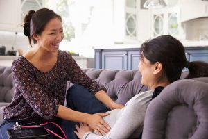 a midwife with a stethoscope feeling a mom's pregnant belly as she reclines on a couch