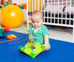 a baby boy playing with a toy on a mat in front of his crib