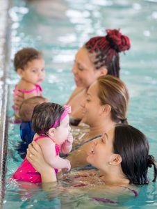 three moms with their babies in a mommy and me swim class