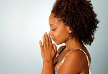a woman with her eyes closed and hands folded in prayer