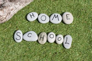 Home School is spelled out on individual rocks in the grass