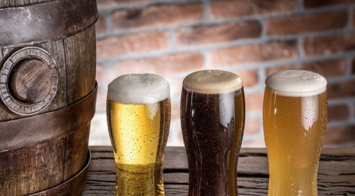 three glasses of foamy craft beer on a wooden plank next to a barrel