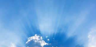 a silver lining as the sun breaks through the dark clouds and shoots rays across the sky
