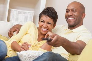 an African American couple sitting on the couch, watching TV with a bowl of popcorn as the man points the remote at the TV