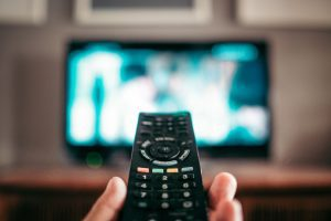 a close up of a hand with a remote, while a TV is blurred in the background