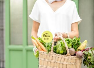 a woman standing in front of a green door with a basket of fresh fruits and vegetables that she will use for cooking