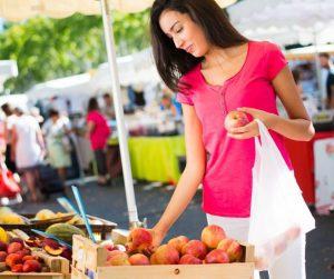 a woman browsing fresh fruits at a farmers market