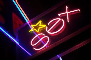 """a neon sign with the word, """"sex"""" in pink with a yellow star over it"""