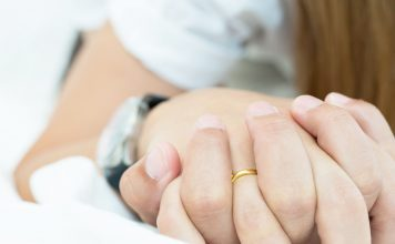 a close up of two people holding hands, one is wearing a wedding ring, as they lay in bed together