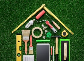 Tools laid out on green turf in the shape of a house to symbolize home renovations and DIY Projects