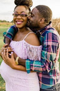 a pregnant woman smiling at the camera as her husband wraps his arms around her and kisses her on the cheek