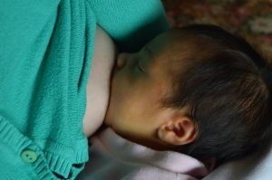 close up of a newborn baby breastfeeding