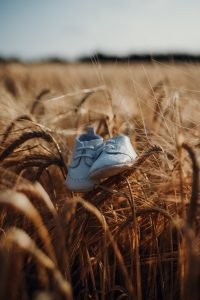 a close up of white baby shoes sitting on top of grass