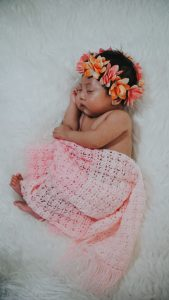 a newborn baby girl swathed in a pink blanket with a crown of flowers on her head