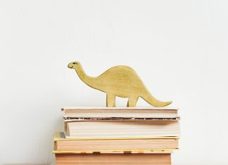 a stack of books with a wooden dinosaur on it