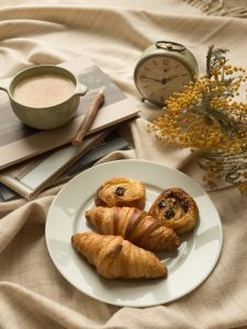 French croissants and pastries with cafe au lait on a table with flowers and an alarm clock