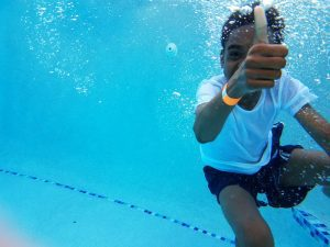 an African American boy swimming underwater as he gives a thumbs up to the camera