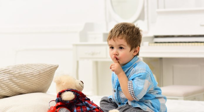 a toddler holding his finger to his lip to shush while he sits on a bed with a teddy bear and alarm clock