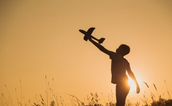 the silhouette of a boy with a toy airplane raised high as the sun sets behind him