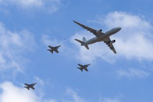 an airplane up in the sky as it is refueling in flight with three smaller planes behind it