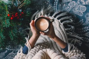 Hands holding hot cup of coffee. Hygge background. Christmas mood.