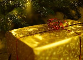 a box wrapped in golden paper with a red bow near the Christmas tree