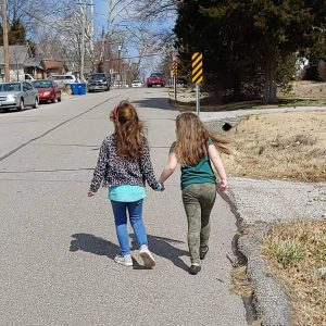 Two neighbor girls, from behind as they hold hands and walk down the street together