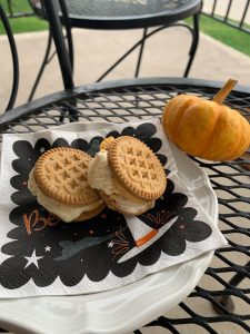 a plate of cookies with ice cream stuffed inside on a white plate with a Halloween napkin to make a simple dessert