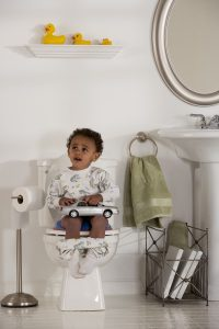 a toddler boy sitting on the toilet as he potty trains