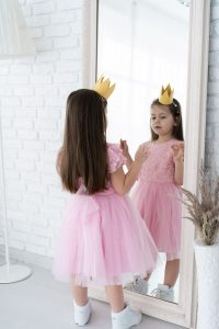 a young girl in a pink dress wearing a gold crown as she looks at herself in a full length mirror