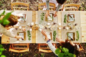 an outdoor table with cream colored placemats, sprigs of greenery, and place settings for a Thanksgiving meal