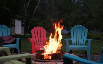 a roaring fire in a fire pit surrounded by empty, multicolored Adirondack chairs