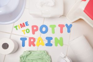 """foam letters spelling """"time to potty train"""" on a white tile floor with toilet paper, wipes, and a potty seat"""