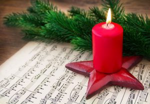 a score of Christmas music on a wooden table with a red, lit candle on top next to a sprig of greenery