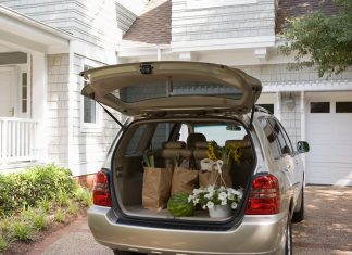 a minivan parked in a driveway with the trunk open and groceries in the back
