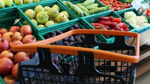 a close up of an empty grocery cart in the produce aisle