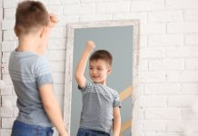 a young boy flexing his muscle as he looks into a mirror