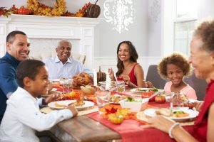 a Thanksgiving table with grandma and grandpa at the heads of the table, with mom and dad with their son and daughter