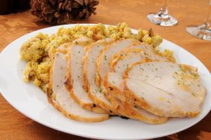 slices of turkey and dressing on a white dinner plate