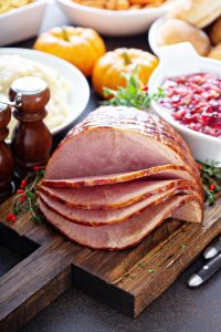 a spiral cut ham on a cutting board with Thanksgiving side dishes in the background