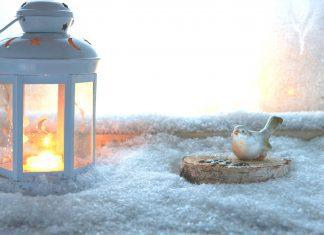 a white lantern lit on a snowy window ledge next to a ceramic bird and nest