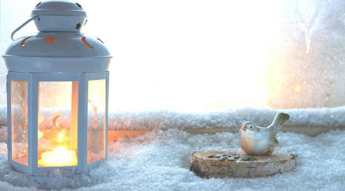 a white lantern lit on a snowy window ledge next to a ceramic bird and nest