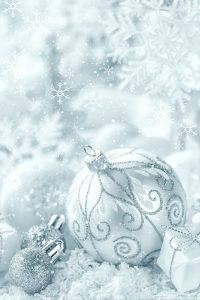 white and silver Christmas ornaments on a bed of soft snow