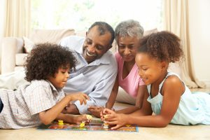 an African American family with grandparents and a young boy and girl laying on the floor playing a board game
