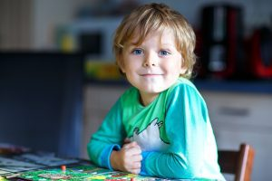 a blonde toddler boy sitting at a table, smiling at the camera as he plays a board game